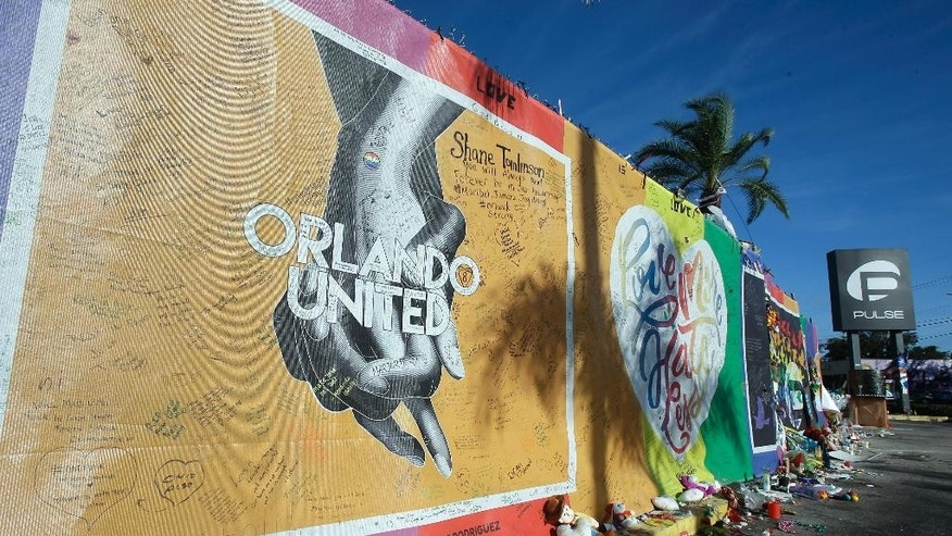 In this Wednesday, Nov. 30, 2016 photo, artwork and signatures cover a fence around the Pulse nightclub, scene of a mass shooting, in Orlando, Fla. A new document from the fire departments that responded to the massacre provides further details on the role of bomb-sniffing dogs during the three-hour standoff. (AP Photo/John Raoux)