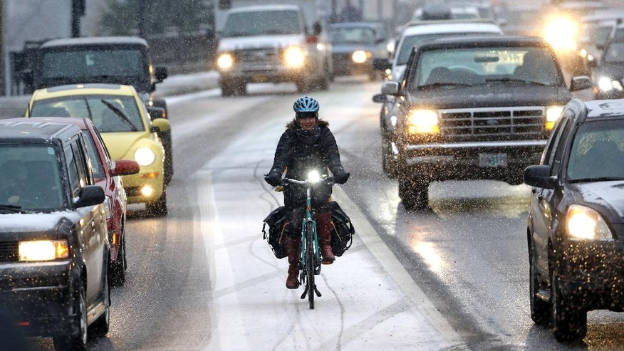 A bicyclist is surrounded by heavy traffic as a snow storm forces commuters to leave the city early and jam roads and freeways in Portland, Ore., Wednesday, Dec. 14, 2016. A wintry afternoon and evening is forecast for much of Oregon, with some cities expected to get a foot of snow.(AP Photo/Don Ryan)