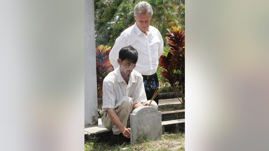 FILE - In this Saturday, March 15, 2008 file photo, My Lai Massacre survivor Do Ba, 48, left, of Ho Chi Minh city, places incense at his family's grave site during the 40 year anniversary of the incident in My Lai, Quang Ngai Province, Vietnam, accompanied by former U.S. Army officer Lawrence Colburn, 58, of Canton, Ga., who rescued Do Ba during the massacre. Colburn, the helicopter gunner who helped end the slaughter of hundreds of unarmed Vietnamese villagers on March 16, 1968, during the Vietnam War has died. He was 67. (AP Photo/Chitose Suzuki)