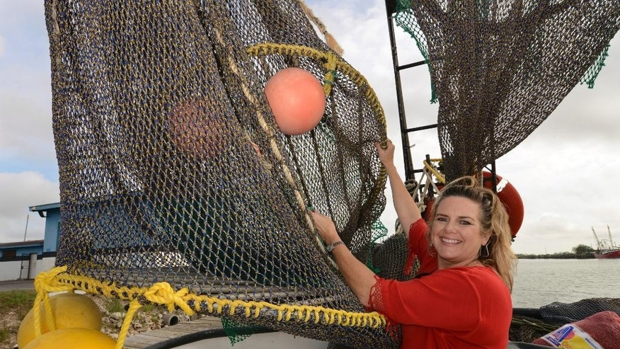 FILE - In this Friday, Dec. 5, 2014 file photo, Andrea Hance, Texas Shrimp Association executive director, poses with a TED, or turtle excluder device, on board a shrimp boat at the Brownsville Shrimp Basin in Brownsville, Texas.  Under proposed new federal rules released on Thursday, Dec. 15, 2016, more shrimp fishermen would have to use nets equipped with turtle escape hatches, to prevent sea turtle deaths.   (Brad Doherty/The Brownsville Herald via AP, File)