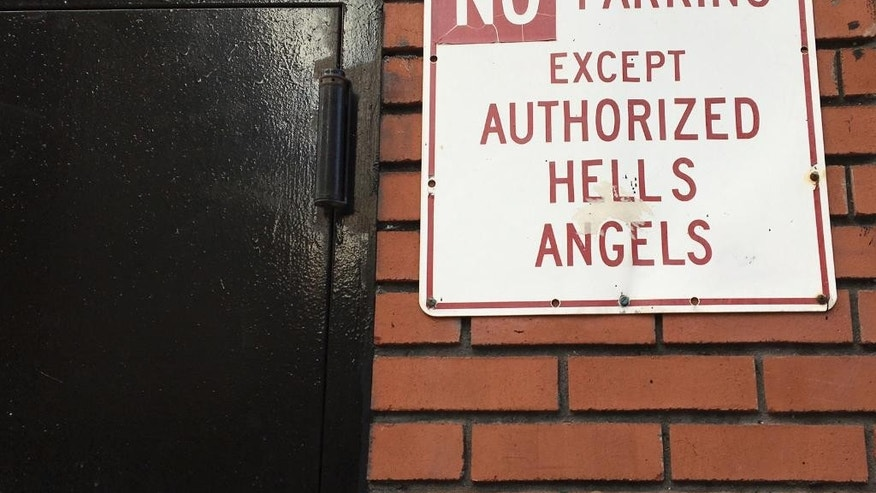 "A sign near the front door of the Hells Angels motorcycle club headquarters in New York reads ""No Parking Except Authorized Hells Angels,"" Friday, Dec. 16, 2016. The latest clash between New York City Police and the Hells Angels came after a man from upstate New York tried to move an orange cone meant to hold a sparking spot for club members and ended up hospitalized with a gunshot wound. (AP Photo/Tom Hays)"