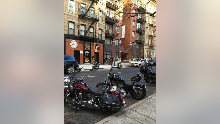 Motorcycles are parked on the street outside the Hells Angels motorcycle club headquarters in New York, Friday, Dec. 16, 2016. Earlier in the week, a man from upstate New York tried to move tried to move one of the orange traffic cones the bikers used to hold curbside parking spots and ended up hospitalized with a gunshot wound. (AP Photo/Tom Hays)