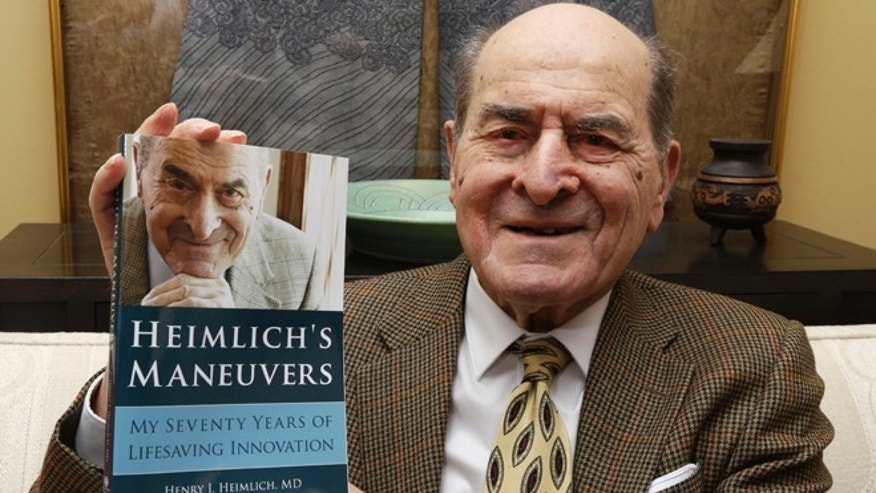 Dr. Henry Heimlich holds his memoir in 2014 photo.