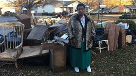 In this Dec. 1, 2016 photo, Dianne Hines stands in front of the mound of furniture and other belongings pulled from her home after Hurricane Matthew, in Princeville, N.C. Hines' home was rebuilt after Hurricane Floyd in 1999. This time, she said she's ready to move elsewhere. (AP Photo/Martha Waggoner)