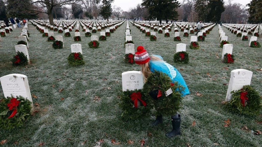 Madeline Espinosa, 11, of Bethesda, Md., places a wreath at a grave as part of Wreaths Across America at Arlington National Cemetery, Saturday, Dec. 17, 2016 in Arlington, Va. Organizers estimate more than 245,000 wreaths were placed at graves throughout the cemetery. (AP Photo/Alex Brandon)