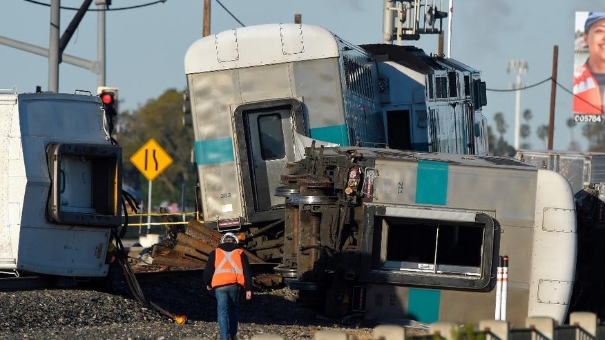 FILE - In this Feb. 24, 2015 file photo, a worker walks along the tracks near the wreck of a Metrolink passenger train that derailed in Oxnard, Calif. Federal investigators have determined that the crash that killed a Metrolink commuter train engineer was probably due to acute fatigue and lack of familiarity with the area by the driver of a utility truck that turned onto the tracks according to the National Transportation Safety Board's final report released Monday, Dec. 19, 2016. (AP Photo/Mark J. Terrill, File)