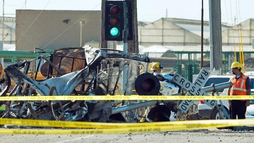 FILE - In this Feb. 24, 2015 file photo, a worker stands next to a railroad crossing sign and the wreckage of a truck that was struck by a Metrolink passenger train, causing it to derail in Oxnard, Calif. Federal investigators have determined that the crash that killed a Metrolink commuter train engineer was probably due to acute fatigue and lack of familiarity with the area by the driver of a utility truck that turned onto the tracks according to the National Transportation Safety Board's final report released Monday, Dec. 19, 2016. (AP Photo/Mark J. Terrill, File)