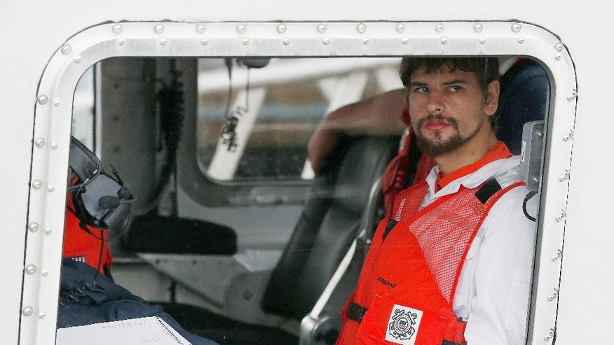 FILE- In this Sept. 27, 2016, file photo, Nathan Carman arrives in a small boat at the US Coast Guard station in Boston. Carman spent a week at sea in a life raft before being rescued by a passing freighter. Police have returned to the home of a man whose 2013 killing remains unsolved and whose daughter is presumed dead after she went out sailing with her son, Nathan Carman, and their boat sank this year. (AP Photo/Michael Dwyer, File)