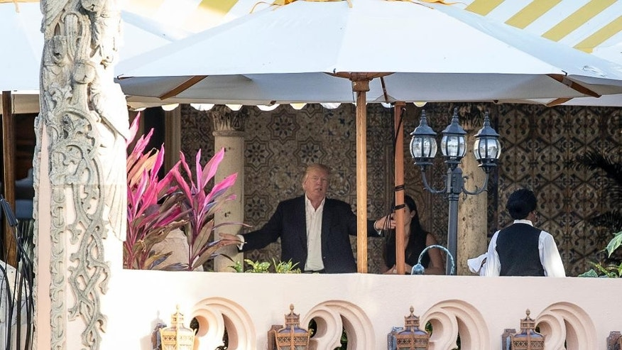 President-elect Donald Trump, center, speaks to an aide at Mar-a-Lago resort, in Palm Beach, Fla., Monday, Dec. 19, 2016. Trump is spending the day in meetings at the resort. (AP Photo/Andrew Harnik)