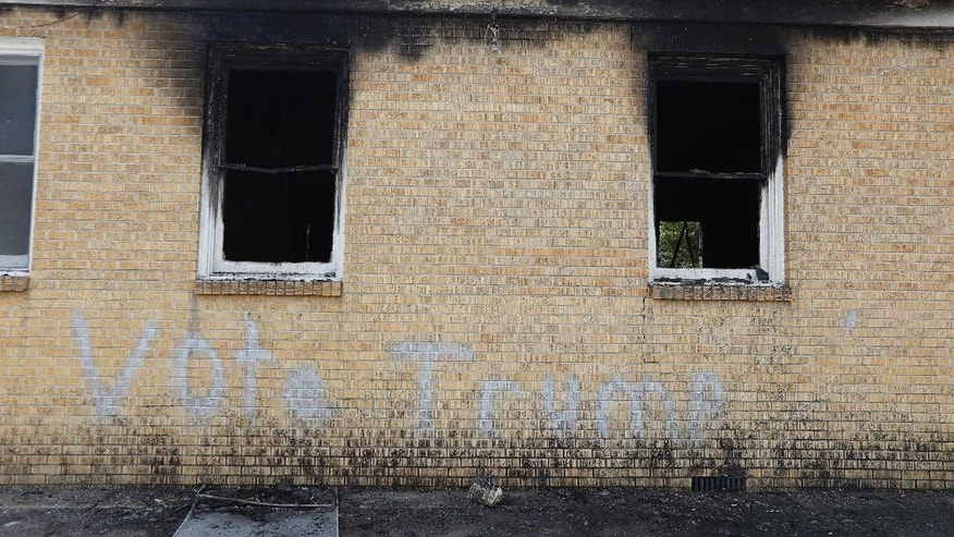 "FILE-In this Wednesday, Nov. 2, 2016 file photo, ""Vote Trump"" is spray painted on the side of the fire damaged Hopewell M.B. Baptist Church in Greenville, Miss. Mississippi authorities arrested a McClinton Wednesday in the burning of an African-American church that was also spray-painted with the words, ""Vote Trump."" (AP Photo/Rogelio V. Solis, File)"