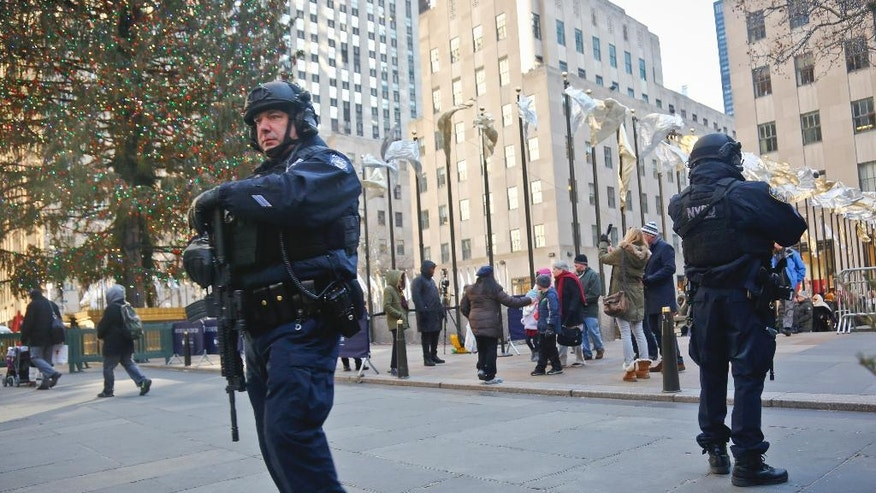 FILE - In this Dec. 20, 2016 file photo, New York City Police patrol near the Christmas tree at Rockefeller Center in New York. New York City Mayor Bill de Blasio says police are reinforcing various Christmas market locations around the city in the wake of the attack in Berlin, Germany that killed 12 people and wounded nearly 50 people. (AP Photo/Bebeto Matthews, File)