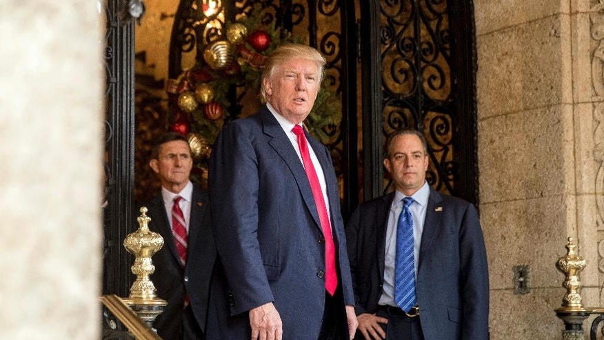 President-elect Donald Trump, center, accompanied by Trump Chief of Staff Reince Priebus, right, and Retired Gen. Michael Flynn, a senior adviser to Trump, left, takes a question from a member of the media at Mar-a-Lago, in Palm Beach, Fla., Wednesday, Dec. 21, 2016. (AP Photo/Andrew Harnik)