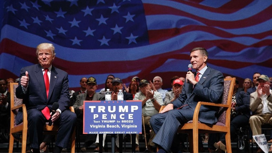 FILE - In this Sept. 6, 2016, file photo, then Republican presidential candidate Donald Trump gives a thumbs-up as he speaks with retired Lt. Gen. Michael Flynn during a town hall in Virginia Beach, Va. Trump is poised to meet with his incoming national security adviser, Flynn, on Wednesday, Dec. 21, in the aftermath of a rattling day of violence around the world. (AP Photo/Evan Vucci, File)