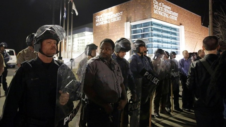 March 11, 2015: Police form a line outside the Ferguson Police Department as people demonstrate in Ferguson, Mo. Earlier in the day, the resignation of Ferguson police chief Thomas Jackson was announced in the wake of a scathing Justice Department report.