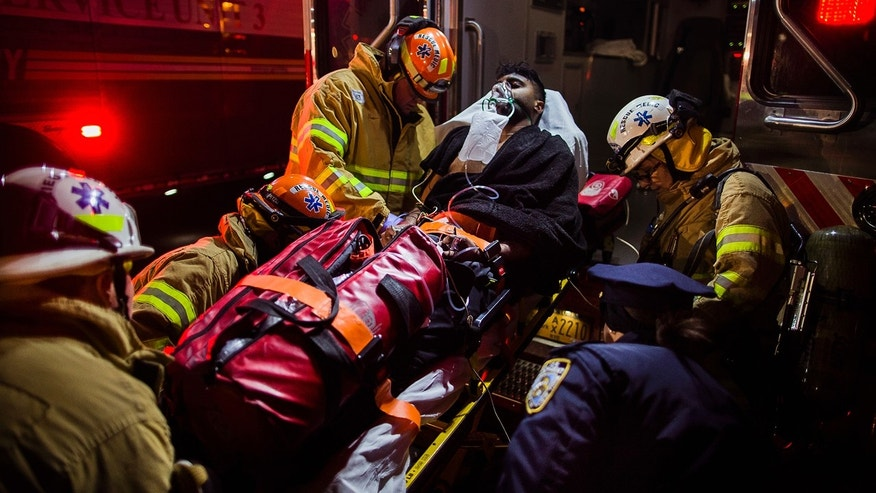 Dec. 22, 2016: Firefighters load an injured person into an ambulance during a fire on the west side of Manhattan in New York