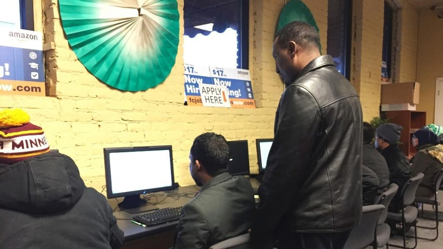 In this Dec. 20, 2016 photo, several people use self-help computers at an employment center in the heart of Minneapolis' largest Somali neighborhood. The center, which connects job seekers to employers, was created with grant money as part of a federal pilot project designed to combat terror recruitment by creating positive opportunities for youth. (AP Photo/Amy Forliti)