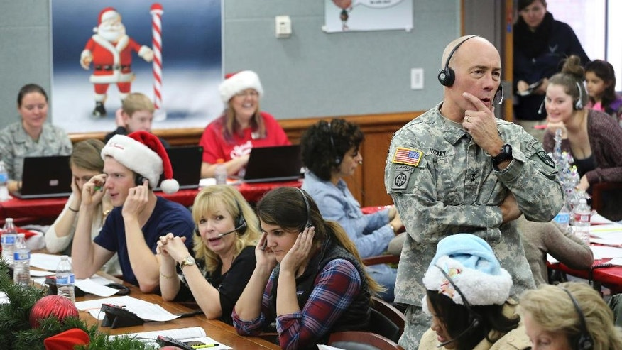 FILE - In this Dec. 24, 2014, file photo, NORAD and U.S. Northern Command (USNORTHCOM) Chief of Staff Maj. Gen. Charles D. Luckey joins other volunteers taking phone calls from children around the world asking where Santa is and when he will deliver presents to their homes, inside a phone-in center during the annual NORAD Tracks Santa Operation, at the North American Aerospace Defense Command, at Peterson Air Force Base, Colo. The wildly popular NORAD Tracks Santa operation is launching its 61st run at Peterson Air Force Base, Colo. Volunteers will answer phone calls and emails and post updates about Santa's storybook world tour on Facebook and Twitter. (AP Photo/Brennan Linsley, File)