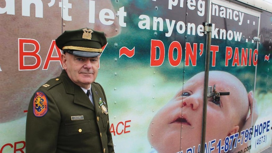 "In this Dec. 12, 2016 photo, Tim Jaccard stands in front of a trailer in Wantagh, N.Y., that advertises a hotline where mothers can call to arrange to safely relinquish babies they are unwilling or unable to care for, to a responsible party. The retired ambulance medic lobbied legislatures across the country to pass so-called ""Safe Haven"" laws in all 50 states. (AP Photo/Frank Eltman)"