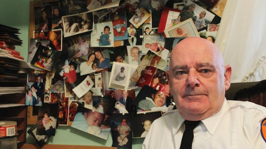 "In this Dec. 12, 2016 photo, Tim Jaccard sits in front of snapshots of some of the children who were safely relinquished under a ""Safe Haven"" program he started 17 years ago, in Wantagh, N.Y. The retired ambulance medic lobbied legislatures across the country to pass so-called ""Safe Haven"" laws in all 50 states. (AP Photo/Frank Eltman)"