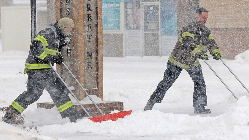 Dec. 25, 2016: Mandan firefighters Shane Weltikol, left, and Chad Nicklos clear accumulating snow from outside the firehouse in downtown Mandan, N.D., as the Christmas Day blizzard intensifies.