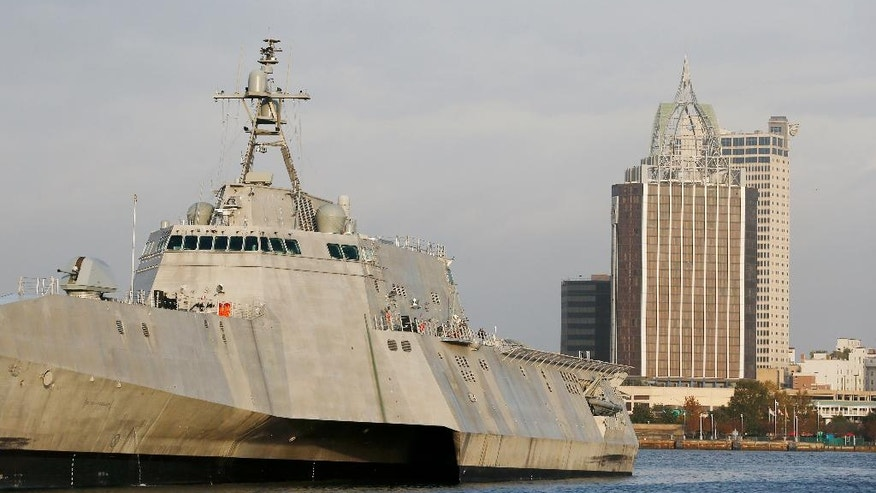 "In this Wednesday, Nov. 30, 2016, photo, the city scape of Mobile, Ala., is seen behind the docked USS Gabrielle Giffords, a Naval littoral combat ship built at the Austal USA shipyards on the Mobile River in Mobile, Ala. The ship is named in honor of former U.S. Rep. Gabrielle ""Gabby"" Giffords of Arizona. Giffords, the former Arizona congresswoman who was shot in the head during an assassination attempt in 2011, helped christen the ship in 2015. It's part of a hotly debated program that congressional critics slam as flawed and too expensive but that Navy leaders defend as a critical new step in naval warfighting. (AP Photo/Brynn Anderson)"