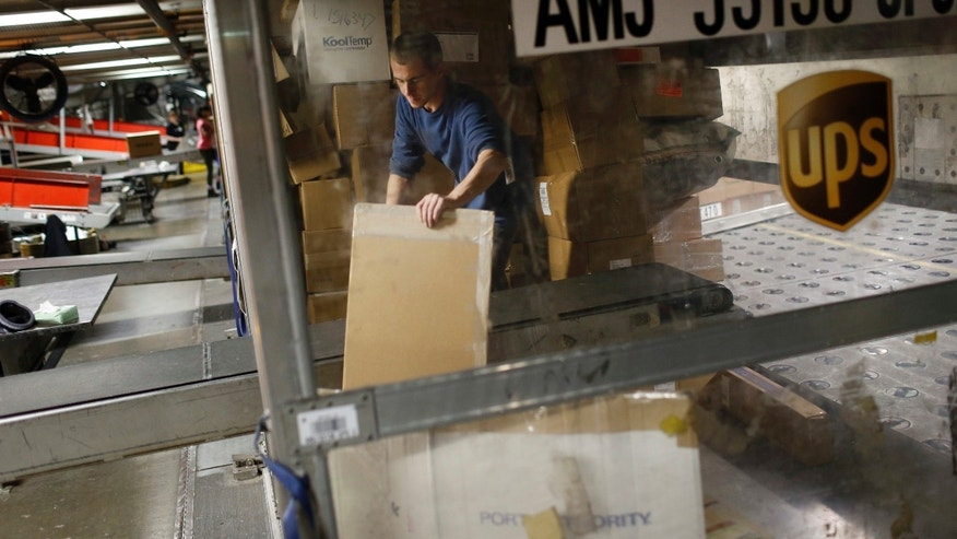 "FILE - In this Nov. 20, 2015, file photo, UPS employee Justin Sims prepares to place a package on a conveyor belt while unloading a container at Worldport in Louisville, Ky. UPS says it will deliver a record 1.3 million returns to retailers on Jan. 5, dubbed ""National Returns Day"" and about 5 million during the first week of 2017. (AP Photo/Patrick Semansky, File)"