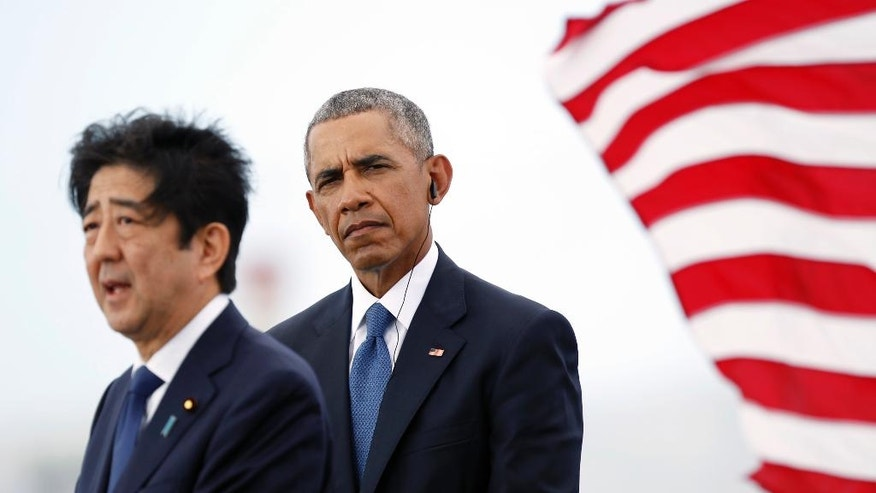 U.S. President Barack Obama listens as Japanese Prime Minister Shinzo Abe speaks on Kilo Pier overlooking the USS Arizona Memorial, part of the World War II Valor in the Pacific National Monument, in Joint Base Pearl Harbor-Hickam, Hawaii, adjacent to Honolulu, Hawaii, Tuesday, Dec. 27, 2016, as part of a ceremony to honor those killed in the Japanese attack on the naval harbor. (AP Photo/Carolyn Kaster)