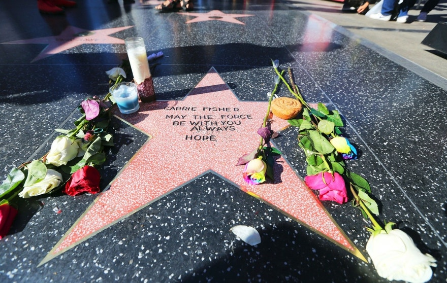 "Flowers and candles adorn an impromptu memorial created on a blank Hollywood Walk of Fame star by fans of late actress and author Carrie Fisher, who does not have an official star on the world-famous promenade, in Los Angeles Wednesday, Dec. 28, 2016. Paste-on letters spell out her name and the phrase ""May the force be with you always. Hope."" (AP Photo/Reed Saxon)"