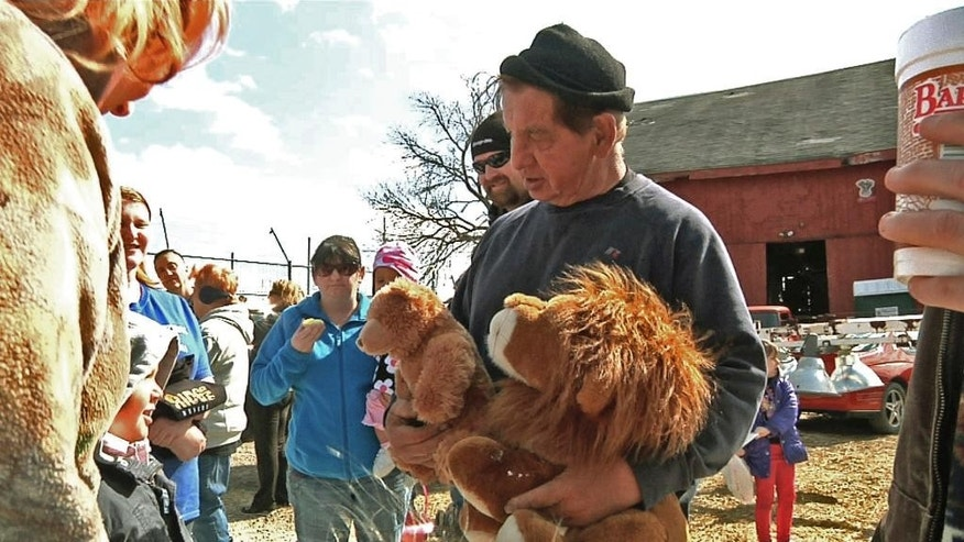 FILE – In this April 4, 2015, file photo, Kenny Hetrick, owner of Tiger Ridge Exotics, holds stuffed toy animals as he speaks to visitors at an Easter egg hunt fundraiser in Stony Ridge, Ohio. Hetrick, who is fighting the state for the return of his tigers and other exotic animals, will be allowed to see some of the animals. A state appeals court said the owner and his veterinarian will be allowed to examine the animals that were sent to a South Dakota sanctuary and later removed from there because of neglect. (AP Photo/Mike Householder, File)