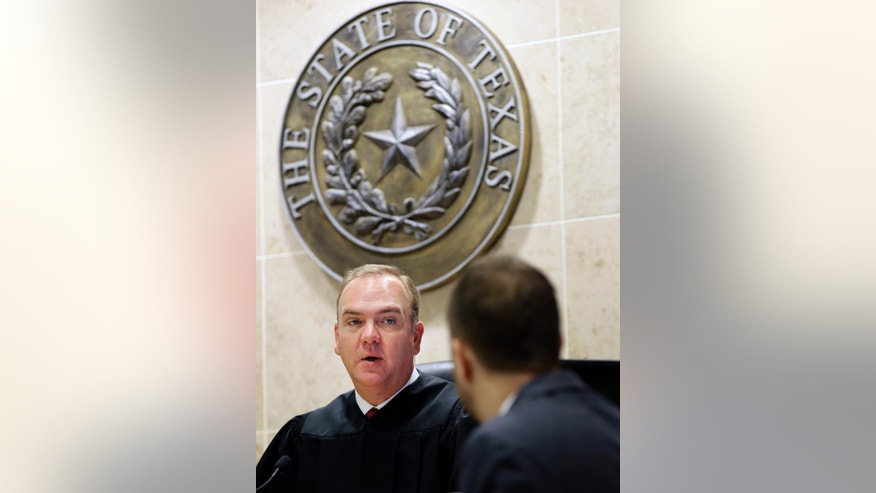 In this Thursday, Dec. 22, 2016 photo, Judge John Roach Jr., left, speaks to a lawyer during a hearing in McKinney, Texas. Rather than requiring veterans to travel to court appearances, Roach Jr.'s court travels to them. The traveling court serves veterans in five counties near Dallas who don't have transportation. Veterans say the opportunity is life-changing. (AP Photo/LM Otero)
