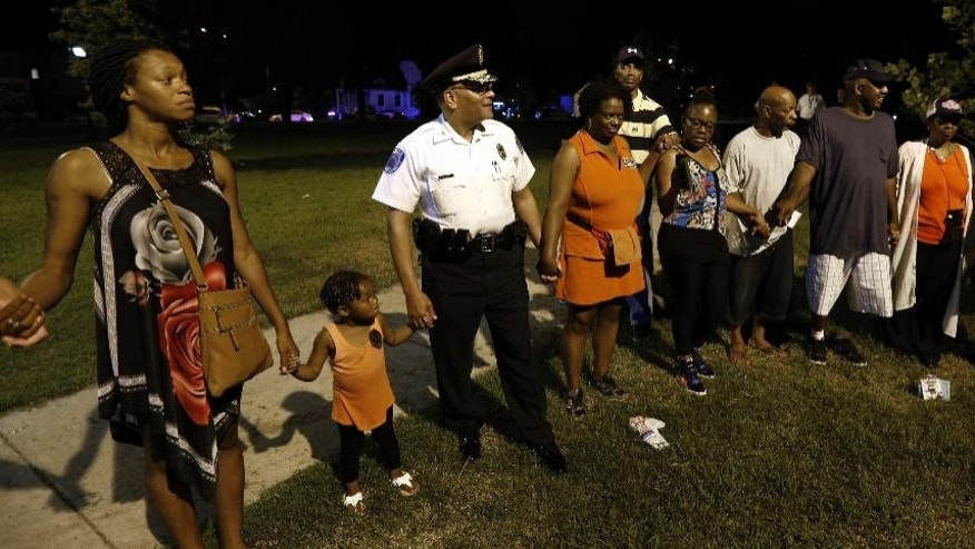 In this Aug. 2, 2016 photo, Richmond Chief of Police Alfred Durham joins with others for prayer during National Night Out festivities at Ann Hardy Park, Va. The deadliest year in Virginia's capital city in a decade has left public officials and residents looking for answers for how to curb the violence. The number of homicides in Richmond is up about 50 percent from last year and is at its highest level since 2006.  (P. Kevin Morley /Richmond Times-Dispatch via AP)