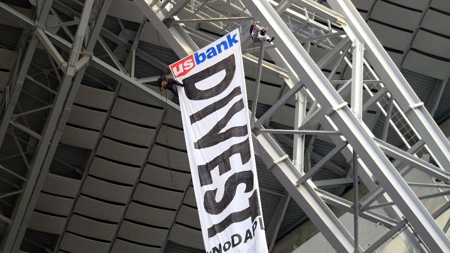 Protesters against the Dakota Access Pipeline rappel from the catwalk in U.S. Bank Stadium during the first half of an NFL football game between the Minnesota Vikings and the Chicago Bears, Sunday, Jan. 1, 2017, in Minneapolis. (AP Photo/Andy Clayton-King)