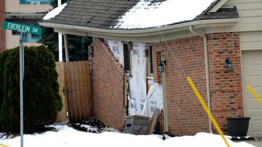 In this Saturday, Dec. 24, 2016 photo, bricks are falling off the exterior wall of a house sitting over a sinkhole, in Fraser, Mich. The major sinkhole disrupted the holiday season in Fraser, a Detroit suburb of roughly 14,500 people about 15 miles north of downtown and five miles west of the Great Lakes waterway of Lake St. Clair. Roads have been closed and about two dozen homes evacuated after the underground sewer collapse on Christmas Eve. Nobody has been injured but inconveniences are many as crews begin a months-long process of assessing the damage, making repairs and determining the cause.   (Todd McInturf/Detroit News via AP)