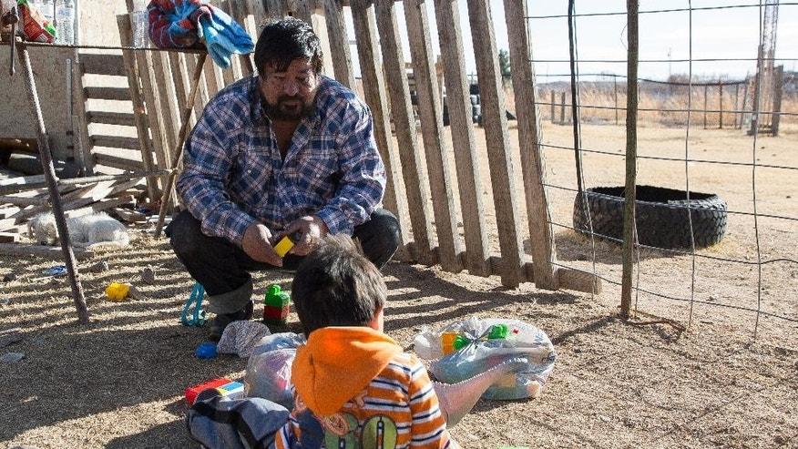 Carlos Jurado plays with his grandson Ethan Jacquez, 2, in the yard near Jurado's home Tuesday, Jan. 3, 2017. in La Mesa, N.M. Dona Ana County sheriff's deputies say Sergio Guadalupe Jacquez turned himself in at the main station Tuesday afternoon. He was accompanied by his attorney, and authorities said he was cooperating with investigators. Authorities planned to book him on charges of arson, aggravated burglary, unlawful taking of a motor vehicle, child abuse and battery. Authorities say the Jacquez had abducted his son Monday. (Josh Bachman/Las Cruces Sun-News via AP)
