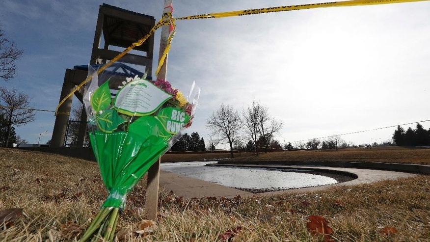 A bouquet of flowers stands below a rope of crime tape around a small, ice-covered lake Tuesday, Jan. 3, in Aurora, Colo. Divers looking for a 6-year-old boy who apparently wandered away from his family's home on New Year's Eve found the body of a child in the lake Tuesday just before noon. An identification has not been made yet, but authorities notified David Puckett's family because of suspicions the body is that of the boy, Aurora Police Chief Nick Metz said.   (AP Photo/David Zalubowski)