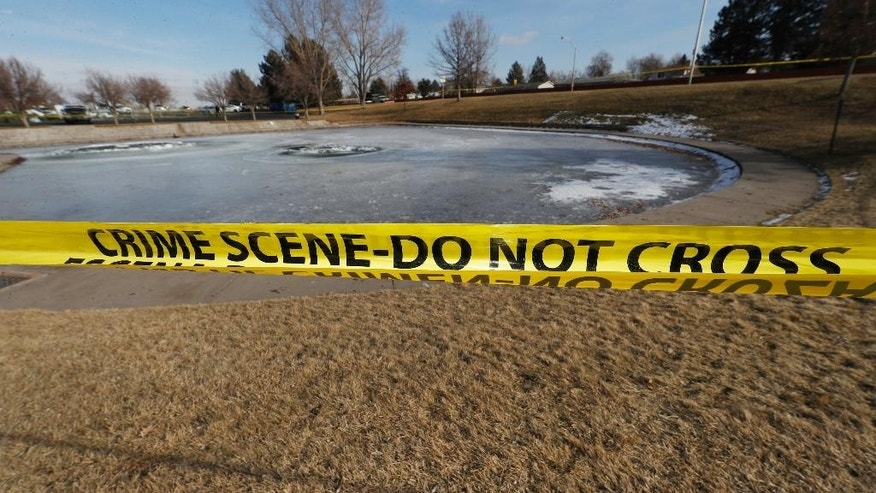 A rope of crime tape is shown around a small, ice-covered lake Tuesday, Jan. 3, 2017, in Aurora, Colo. Divers looking for a 6-year-old boy who apparently wandered away from his family's home on New Year's Eve found the body of a child in the lake Tuesday.  An identification has not been made yet, but authorities notified David Puckett's family because of suspicions the body is that of the boy, Aurora Police Chief Nick Metz said.   (AP Photo/David Zalubowski)