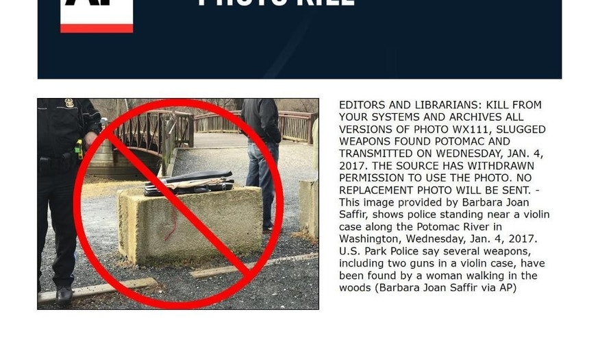 EDITORS AND LIBRARIANS: KILL FROM YOUR SYSTEMS AND ARCHIVES ALL VERSIONS OF PHOTO WX111, SLUGGED WEAPONS FOUND POTOMAC AND TRANSMITTED ON WEDNESDAY, JAN. 4, 2017. THE SOURCE HAS WITHDRAWN PERMISSION TO USE THE PHOTO. NO REPLACEMENT PHOTO WILL BE SENT. -  This image provided by Barbara Joan Saffir, shows police standing near a violin case along the Potomac River in Washington, Wednesday, Jan. 4, 2017. U.S. Park Police say several weapons, including two guns in a violin case, have been found by a woman walking in the woods (Barbara Joan Saffir via AP)