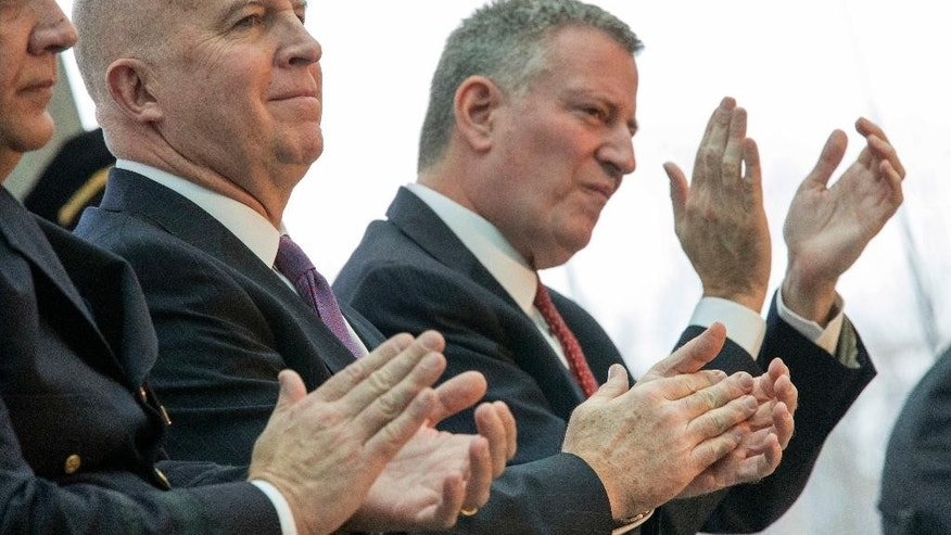 New York City Mayor Bill de Blasio, right, and NYPD Commissioner Jim O'Neil react as a statistic is quoted during a news conference, Wednesday, Jan. 4, 2017, in New York. New York City recorded its fewest number of shootings last year and narrowly missed setting a record low for homicides. According to data released Wednesday, the city had 335 homicides in 2016. The city's record low was 333 in 2014. Police officials reported 998 shooting incidents in 2016. Overall crime was also at its lowest.(AP Photo/Mary Altaffer)
