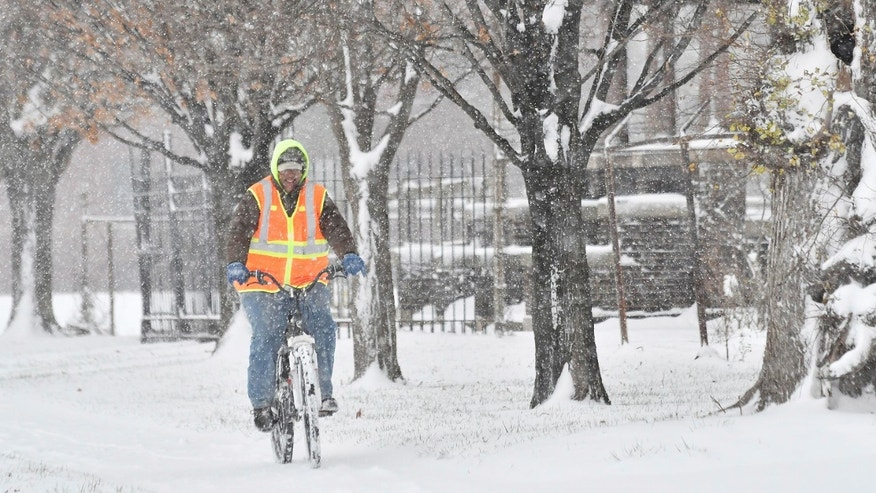 Jacinto L. Santos makes his way through the snow on his bicycle in Detroit, Sunday, Dec. 11, 2016. Santos, originally from Texas, said his mountain bike is his main mode of transportation to work and everywhere. Much of Michigan's southern Lower Peninsula, from Lake Michigan to Lake Huron, is under a winter storm warning. (Robin Buckson/Detroit News via AP)