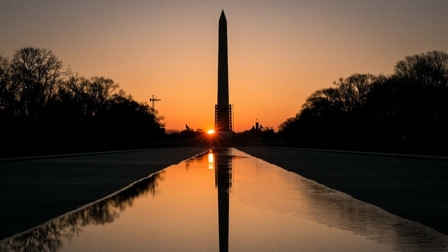 The sun peeks through the scaffolding around the Washington Monument at dawn in Washington.