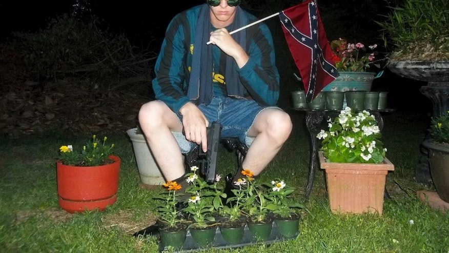 FILE - This undated photo that appeared on Lastrhodesian.com, a website investigated by the FBI in connection with Dylann Roof, shows him posing for a photo holding a Confederate flag. Roof, who would later admit he wanted to start a race war, fatally shot eight black worshippers and their pastor at the Emanuel African Methodist Episcopal Church in Charleston, South Carolina. The following week, Obama delivered the eulogy for the slain Rev. Clementa Pinckney, speaking about the symbolism of the Confederate flag and how racial bias infects everyday life. (Lastrhodesian.com via AP, File)