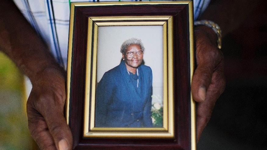 FILE -In this Friday, June 19, 2015 file photo, Walter Jackson holds a photo of his mother Susie Jackson, one of the nine people killed in Wednesday's shooting at Emanuel AME Church by Dylan Roof, as he stands on his front porch, in Charleston, S.C. During Dylan Roof's sentencing for friends and family members walked up to the witness stand and testified about the nine black church members gunned down during a Bible study. The testimony came during the sentencing phase of Dylann Roof's death penalty trial. (AP Photo/David Goldman, File)