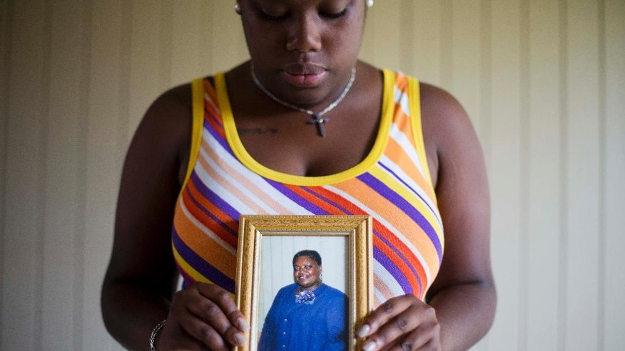"FILE-In this  Friday, June 19, 2015 file photo, Najee Washington holds a photo of her grandmother Ethel Lance, one of the nine people killed in Wednesday's shooting at Emanuel AME Church, by Dylan Roof, as she poses for a portrait outside her home, in Charleston, S.C. ""She cared for everyone.During Dylan Roof's sentencing for friends and family members walked up to the witness stand and testified about the nine black church members gunned down during a Bible study. The testimony came during the sentencing phase of Dylann Roof's death penalty trial. (AP Photo/David Goldman, File)"