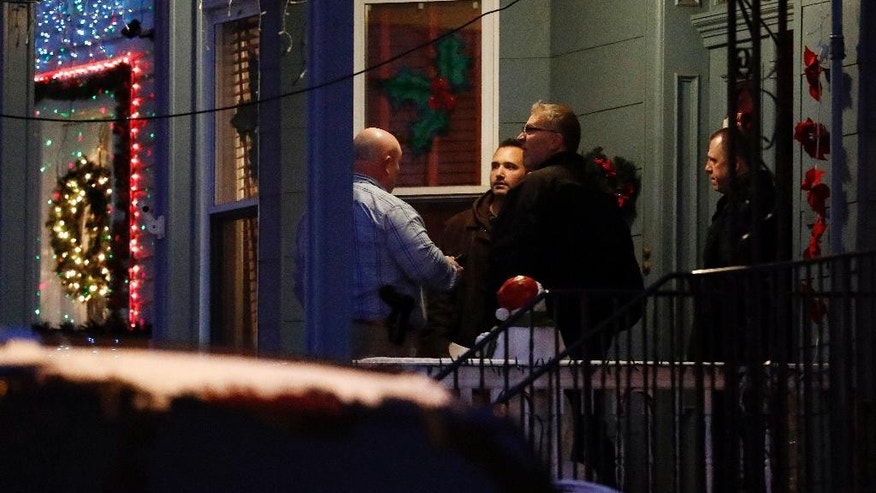People believed to be FBI agents are seen outside of a home believed to be inhabited by possible family members of the suspect in the shooting at the Fort Lauderdale-Hollywood International Airport, Friday, Jan. 6, 2017, in Union City, N.J. (AP Photo/Julio Cortez)