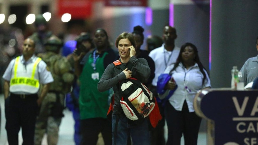 Employees and passengers walk outside terminal 2 at the scene of a deadly shooting at Fort Lauderdale–Hollywood International Airport, Friday, Jan. 6, 2017, in Fort Lauderdale, Fla. An Army veteran who complained that the government was controlling his mind drew a gun from his checked luggage on arrival at the Fort Lauderdale airport and opened fire in the baggage claim area Friday, killing several people and wounding others, authorities said. (David Santiago/El Nuevo Herald via AP)