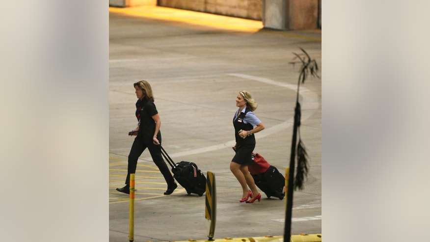 People walk into the parking garage near the scene of a deadly shooting at Fort Lauderdale–Hollywood International Airport, Friday, Jan. 6, 2017, in Fort Lauderdale, Fla. An Army veteran who complained that the government was controlling his mind drew a gun from his checked luggage on arrival at the Fort Lauderdale airport and opened fire in the baggage claim area Friday, killing several people and wounding others, authorities said. (David Santiago/El Nuevo Herald via AP)