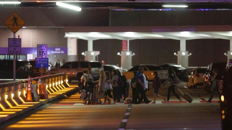 Employees and passengers walk into the parking garage near the scene of a deadly shooting at Fort Lauderdale–Hollywood International Airport, Friday, Jan. 6, 2017, in Fort Lauderdale, Fla. An Army veteran who complained that the government was controlling his mind drew a gun from his checked luggage on arrival at the Fort Lauderdale airport and opened fire in the baggage claim area Friday, killing several people and wounding others, authorities said. (David Santiago/El Nuevo Herald via AP)