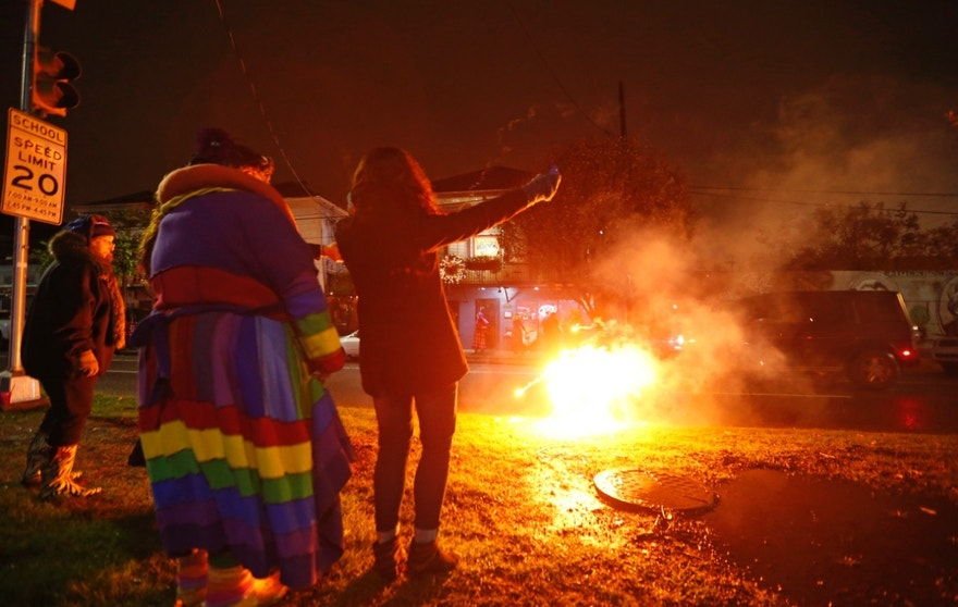 "Revelers of the ""Societe des Champs Elysee"" launch fireworks before boarding the Rampart-St. Claude street car line, which just opened last fall, to commemorate the official start of Mardi Gras season, in New Orleans, Friday, Jan. 6, 2017. Wearing masks and festive costumes, they honored their king and queen at a neighborhood bar and danced as a brass band played ""Carnival Time,"" before boarding their red street car. (AP Photo/Gerald Herbert)"