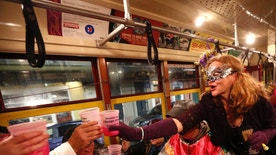 """Members of the """"Societe des Champs Elysee"""" toast as they ride the Rampart-St. Claude street car line, which just opened last fall, to commemorate the official start of Mardi Gras season, in New Orleans, Friday, Jan. 6, 2017. Wearing masks and festive costumes, they honored their king and queen at a neighborhood bar and danced as a brass band played """"Carnival Time,"""" before boarding their red street car. (AP Photo/Gerald Herbert)"""