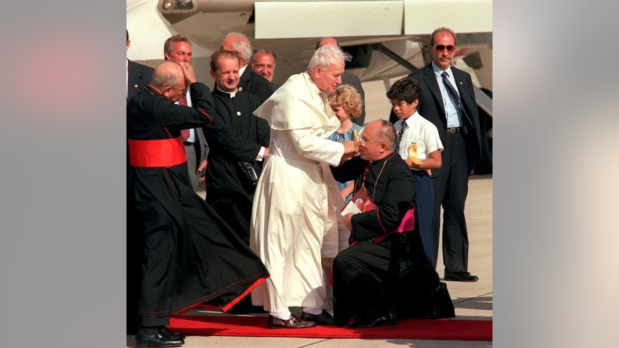 FILE - In this Sept 1987, file photo, Archbishop Patricio Fernandez Flores, front right, kneels and kisses Pope John Paul II's ring as the pope gets off an airplane at Kelly Air Force Base in San Antonio. Flores has died at the age of 87. In a lengthy statement, the San Antonio archdiocese said Flores died Monday, Jan. 9, 2017, of pneumonia and congestive heart failure at a San Antonio assisted living center for retired priests. (Robert McIeroy/The San Antonio Express-News via AP, File)